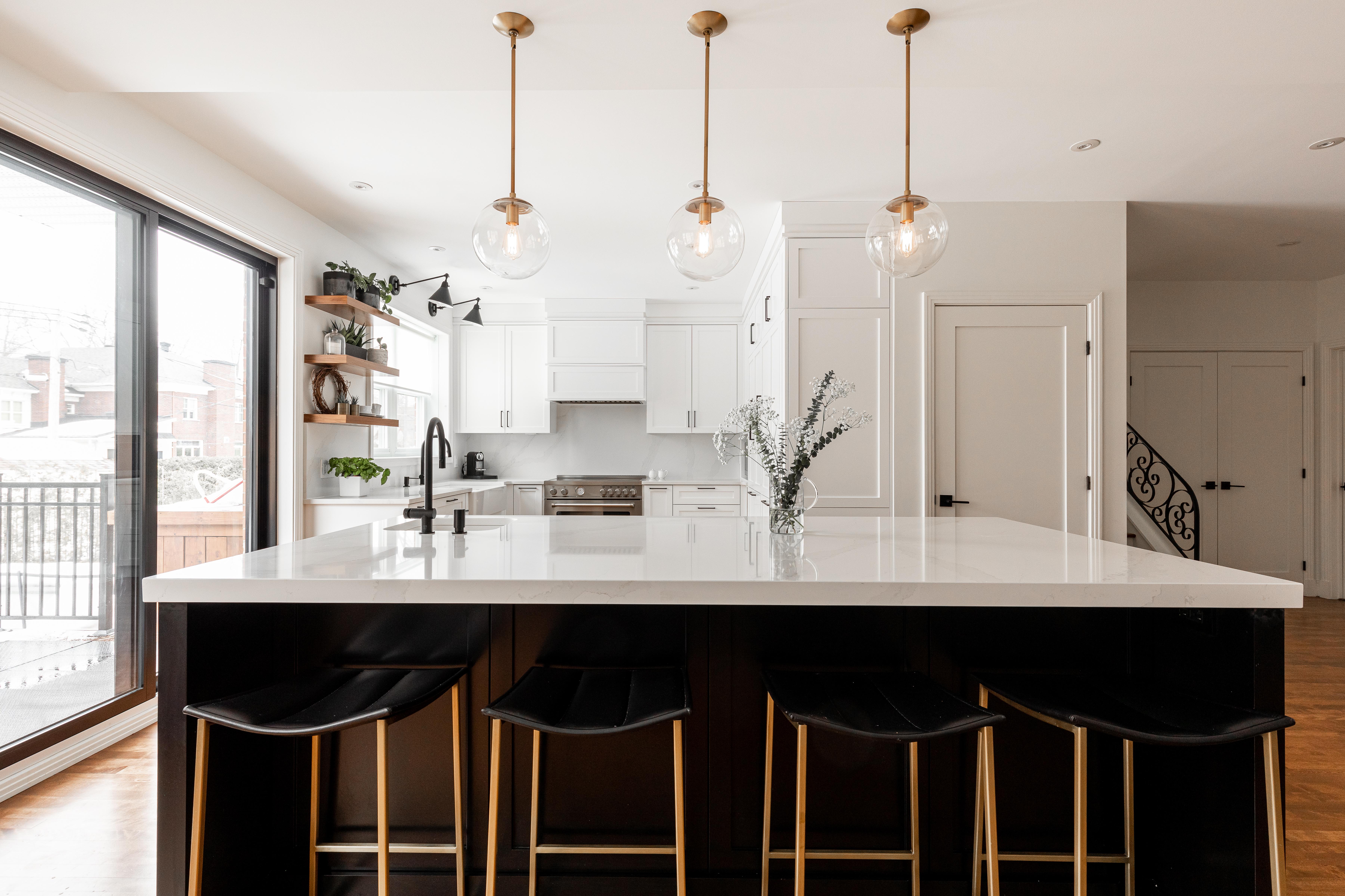 Cuisine moderne. Des luminaires de couleur dorée sont supendus au dessus de l'îlot central de la cuisine.