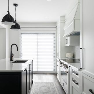 Modern open concept kitchen. The wardrobes of the island are black while those of the main structure are white.