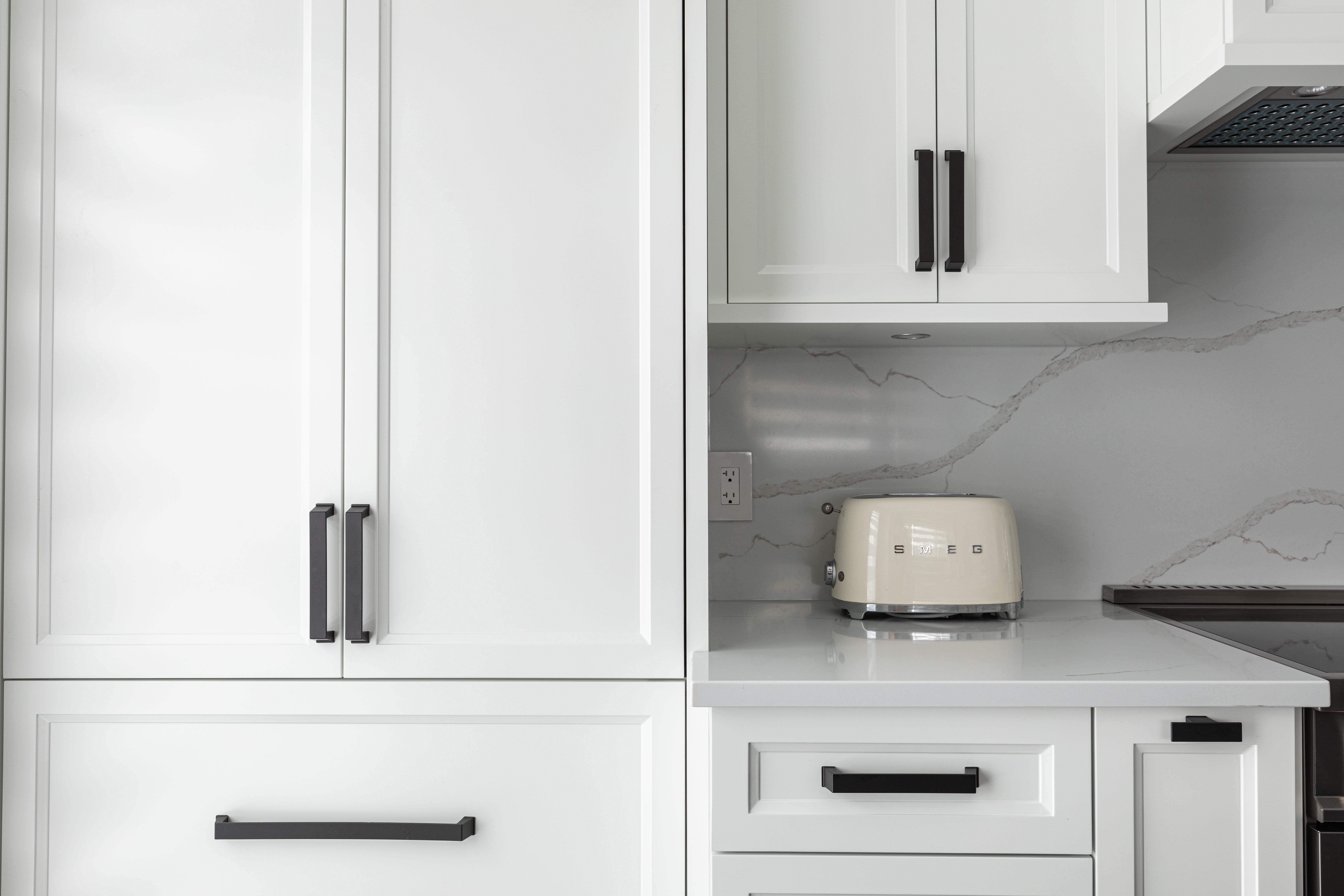 Armoires blanches avec poignées modernes noires et un grille-pain blanc