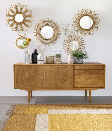 A number of small decorative items are placed on a wooden chest of drawers. Rattan mirrors hang on the wall above the dresser.