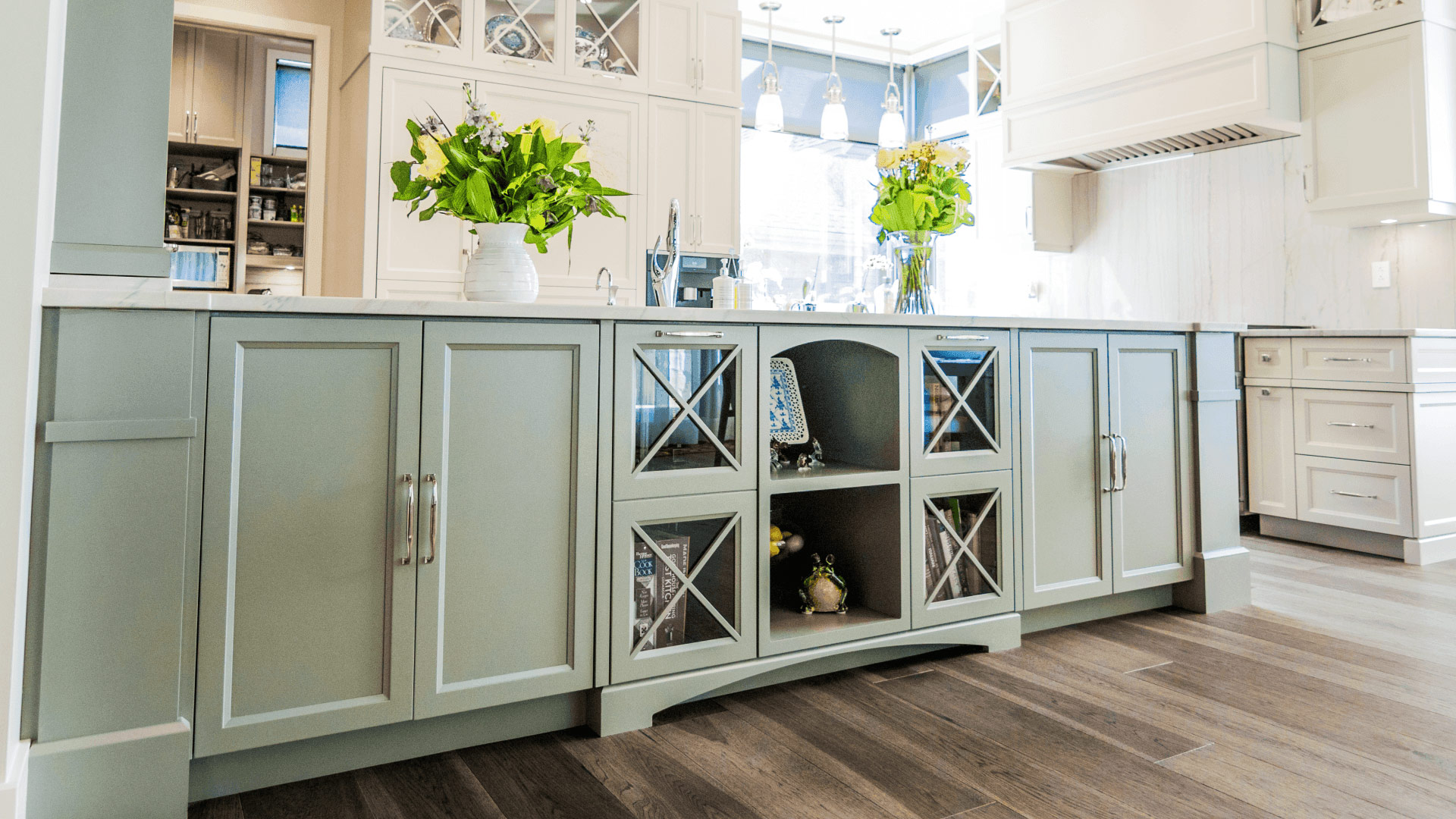 Kitchen cabinets of the central island of a kitchen in soft green color. Some of the wardrobes feature glass doors.