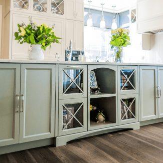 Armoires de cuisine de l'îlot central d'une cuisine de couleur vert tendre. Certaines des armoires arborent des portes en verre.