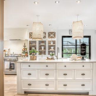 Cuisine de style champêtre réalisée par Ateliers Jacob. Les armoires de cuisine sont en MDF blanc que les insertions de bois sur certains éléments viennent réchauffer. Le comptoir de quartz complète le look avec une touche de finesse. Quelques plantes sont installés sur l'îlot central et les comptoirs.