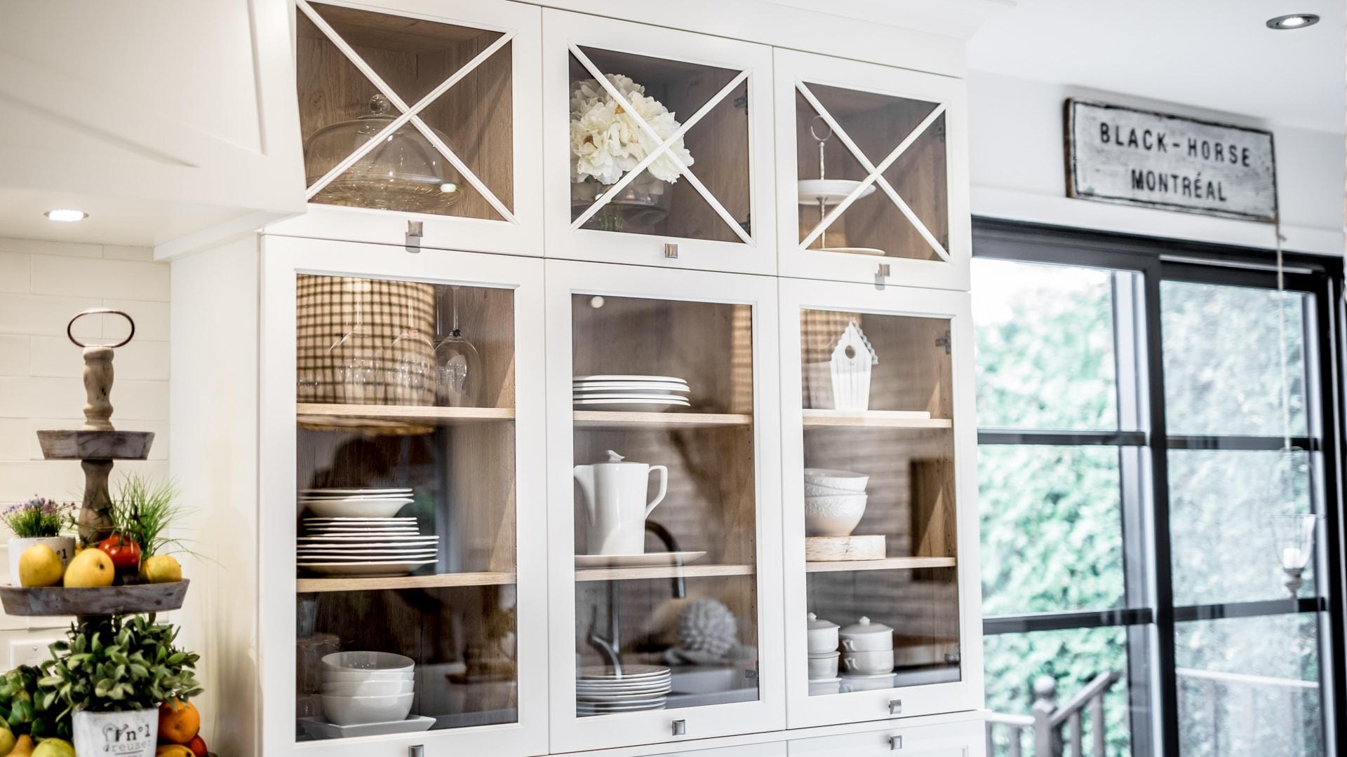 Armoires de cuisine en MDF blanc dont certaines portes sont en verre. La rangée la plus haute de l'armoire possède des portes vitrées dont le cadre se croise sur la vitre.