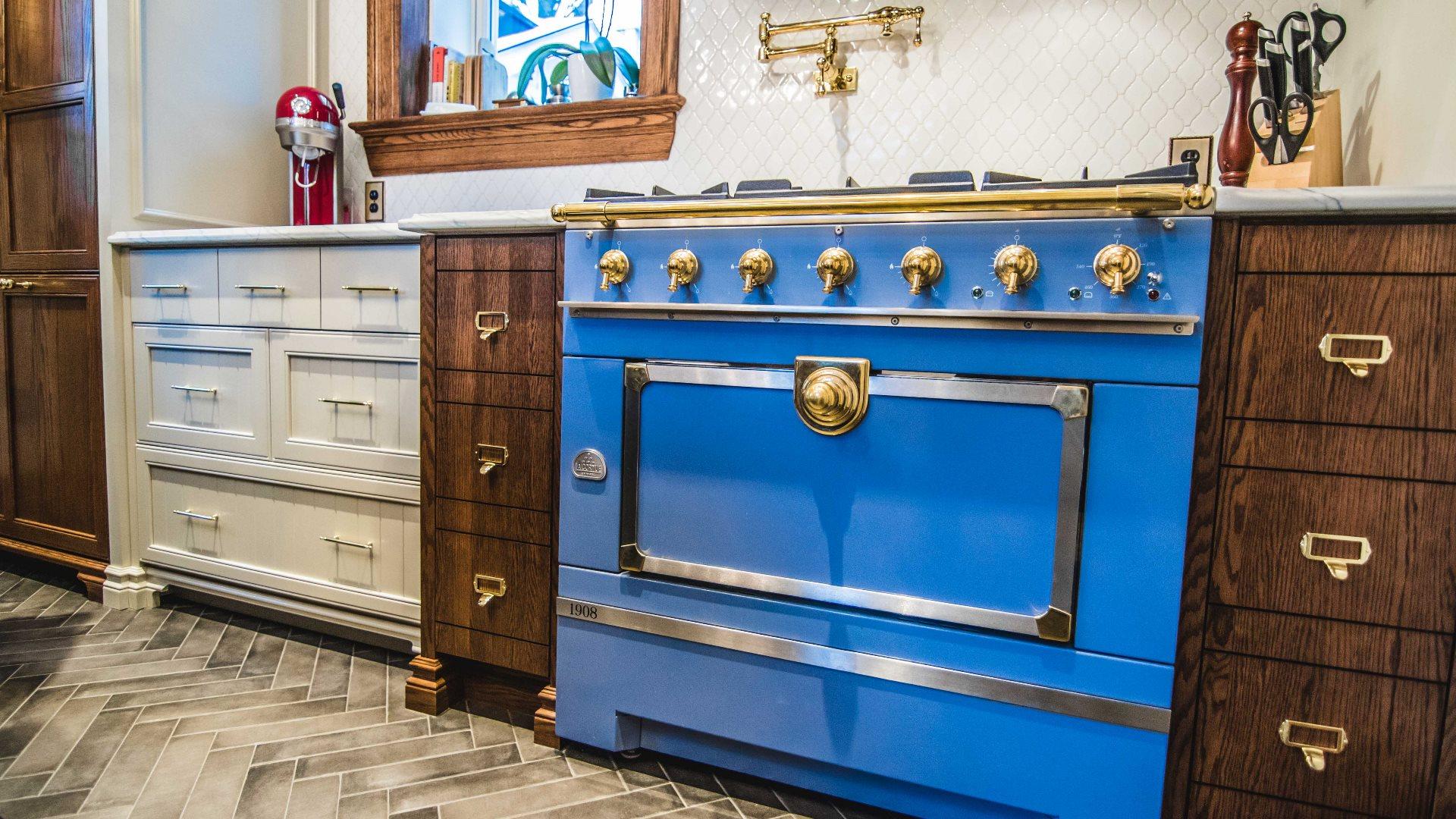 Cuisine classique aux armoires de cuisine en chêne. Un imposant four de couleur bleue est intégré à l'ensemble.