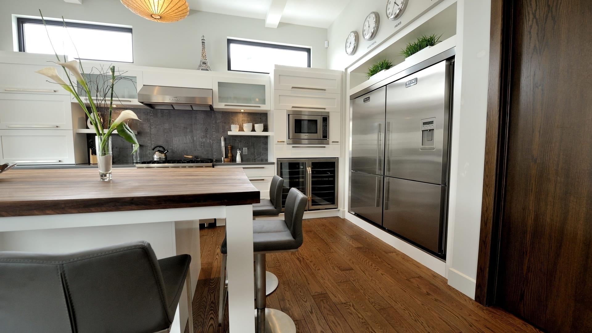 Cuisine contemporaine blanche avec îlot. La cuisine est notamment équipée d'un double frigo encastré dans les armoires de cuisine.