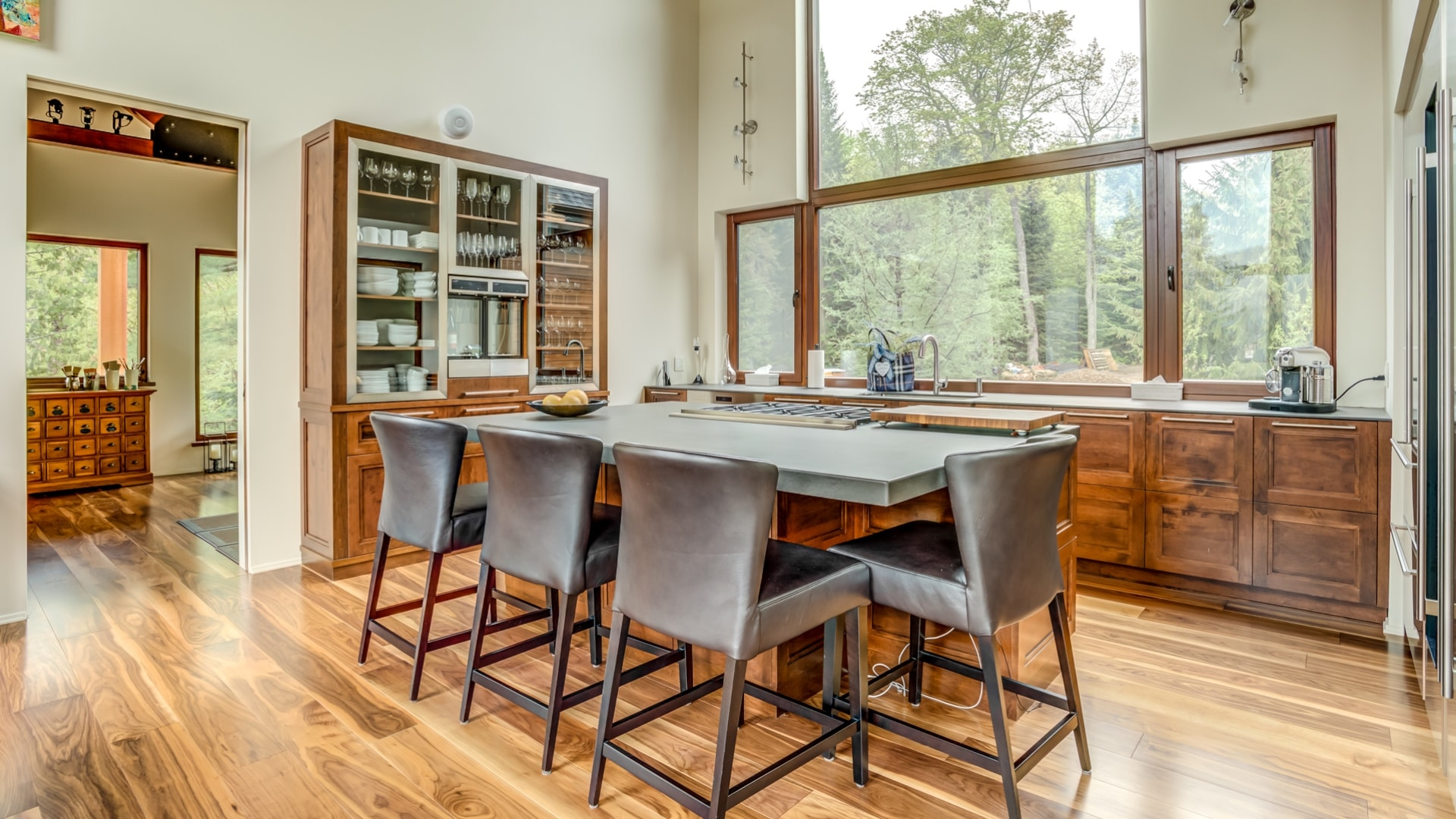 Cuisine contemporaine réalisée par Ateliers Jacob. Les armoires sont faites en érable et les comptoirs en porcelaine Neolith. La cuisine comporte un immense vaisselier.