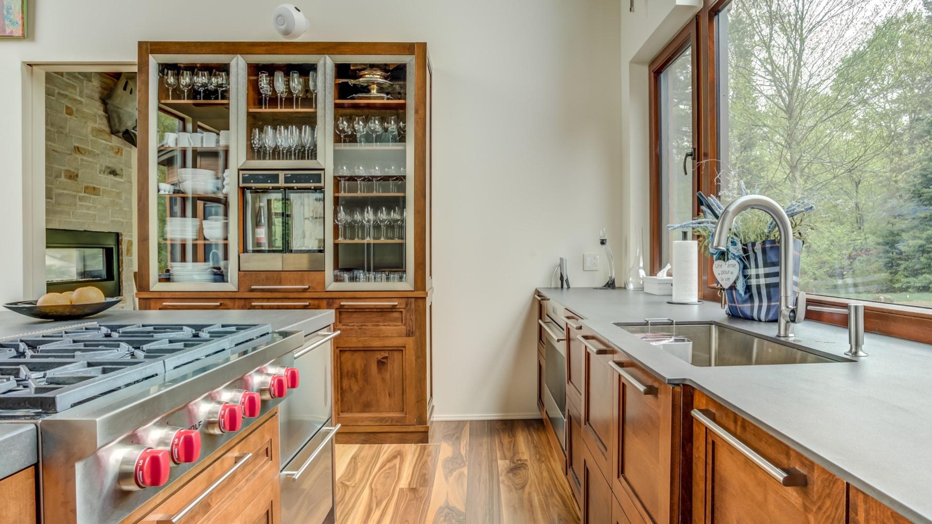 Cuisine contemporaine comprenant une haute armoire en érable. Une partie des portes de cette armoires sont vitrées.