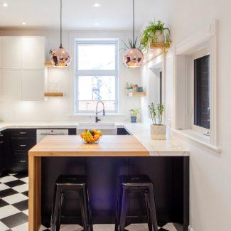 Cuisine urbaine réalisée par Ateliers Jacob. Les armoires de cuisine sont noires et blanches pour s'accorder au sol en damier. Le comptoir de l'îlot central est un épais bloc de boucher en merisier huilé qui contraste avec les autres comptoirs de la cuisine en dekton blanc.