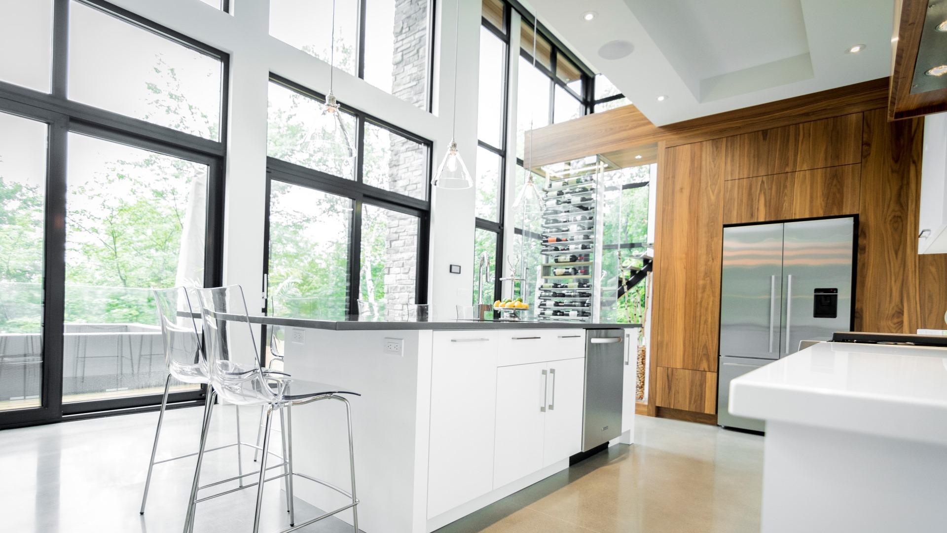 Cuisine moderne à aire ouverte. Le lave-vaisselle est intégré aux armoires de l'îlot central.