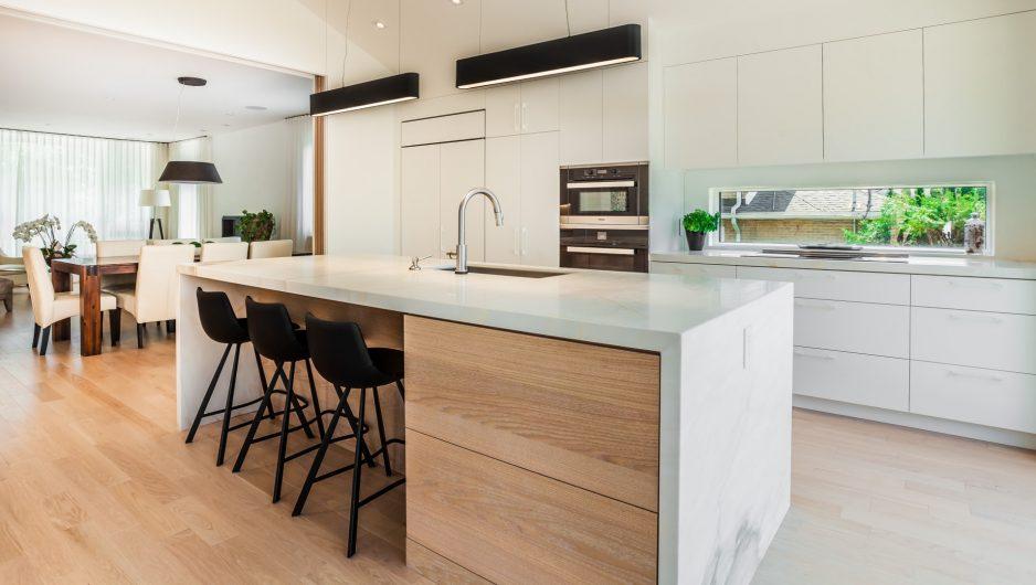 Exemple de cuisine au style scandinave réalisée par Ateliers Jacob. Les matériaux sont clairs : on retrouve du bois et un peu de marbre. Les rangements sont discrets.