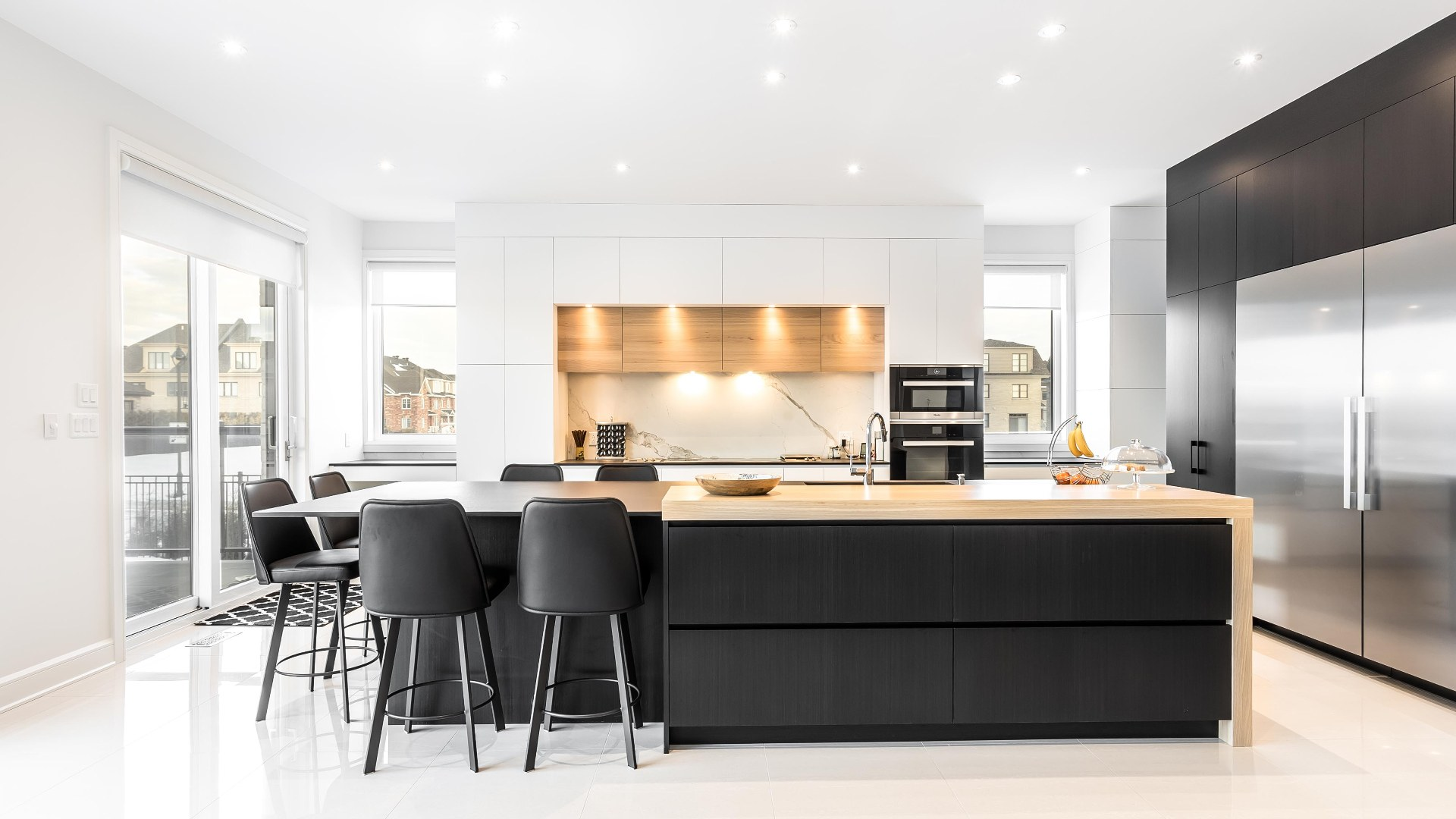 Modern black and white kitchen with Thermoform cabinets accented with oak wood. Luminaires are integrated into kitchen furniture to directly illuminate worktops and counters.