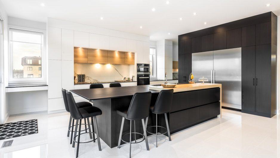 Cuisine moderne noire et blanche composée d'armoires en Thermoform accentuées de bois de chêne. L'îlot central est prolongé d'une table de manger autour de laquelle six tabourets sont disposés.