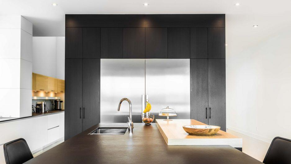 Cuisine moderne comportant un large comptoir en bois ainsi qu'un double frigo intégré à des arrmoires également en bois.
