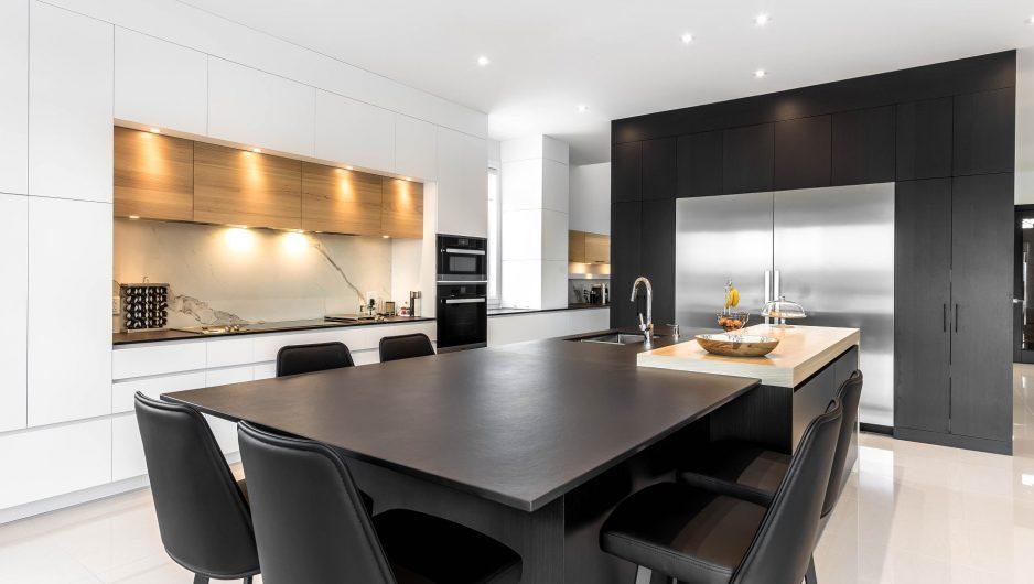 Cuisine moderne noire et blanche composée d'armoires en Thermoform accentuées de bois de chêne. La cuisine comporte un très large double frigo, un four, un micro-ondes et de nombreux équipements.