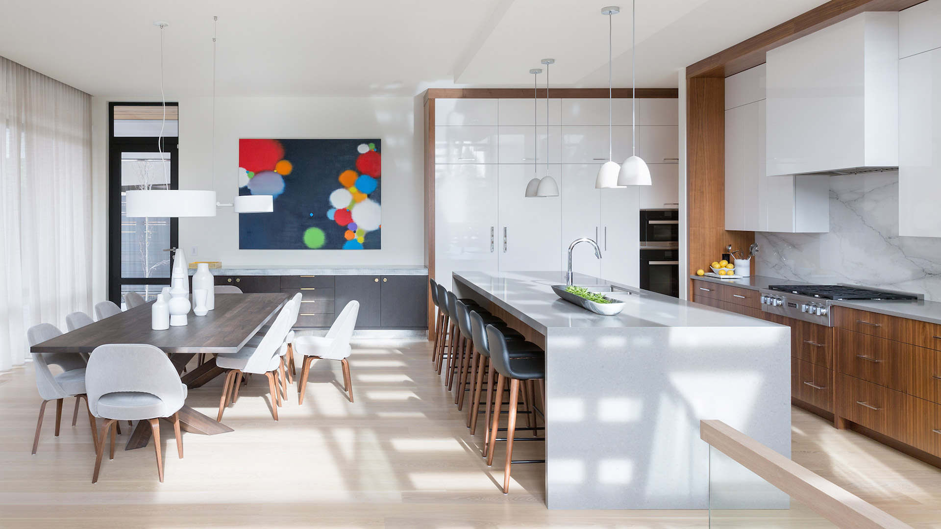 Cuisine moderne réalisée par Ateliers Jacob. Les armoires et la table en bois contrastent très joliment avec la blancheur du comptoir et du mur en marbre intégré.