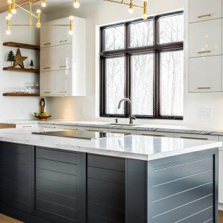 Cuisine transitionnelle réalisée par Ateliers Jacob. Les armoires de cuisine sont blanches et en polymère. L'îlot central est en en HDF laqué bleu. Les comptoirs sont tous en quartz. Une jolie banquette en polymère blanc lustré est intégrée au coin lunch de la cuisine. Les poignées de porte dorées accuentuent l'ensemble.