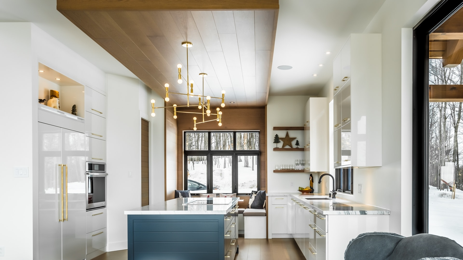 Transitional cuisine. A gold-colored metal light is suspended above the island.