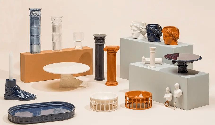 Quelques éléments de décoration antique disposés pour une séance photo : de la poterie, des minis statues ou encore des bougeoires