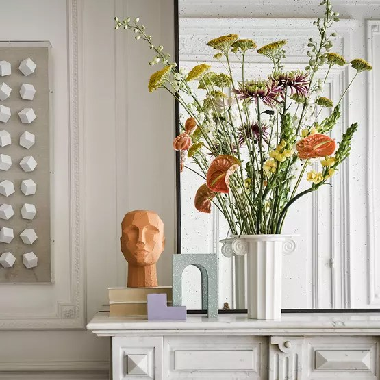 A few antic-style decorative objects adorn a marble fireplace, in addition to a vase containing flowers.