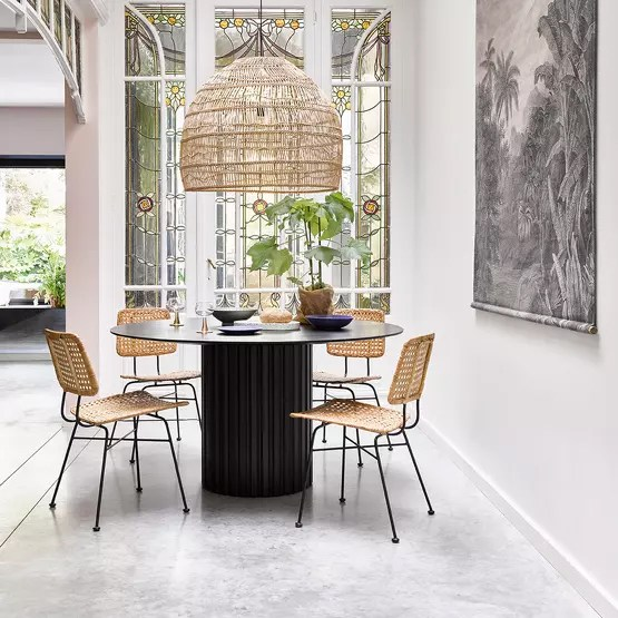 Black massive antique style table paired with modern chairs