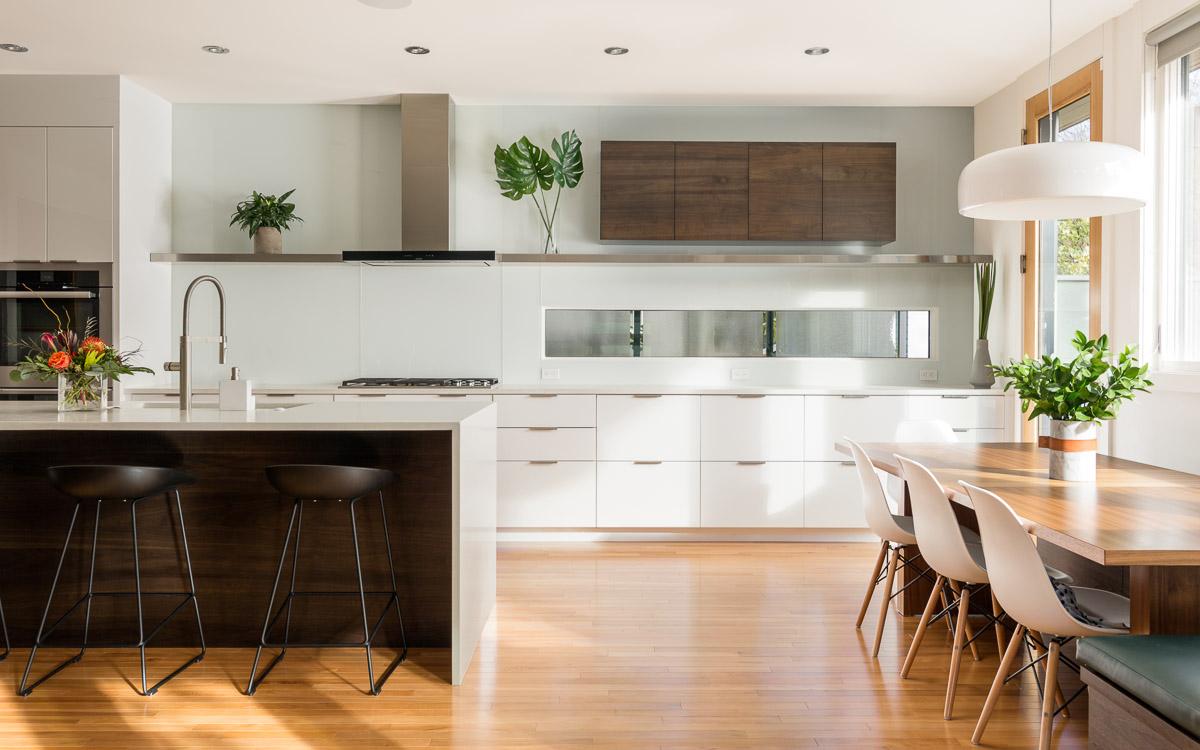 Cette cuisine lumineuse possède un ilot brun sur la gacuhe, une table longue en bosi clair sur la droite et dans le fond des armoires de cuisine blanche
