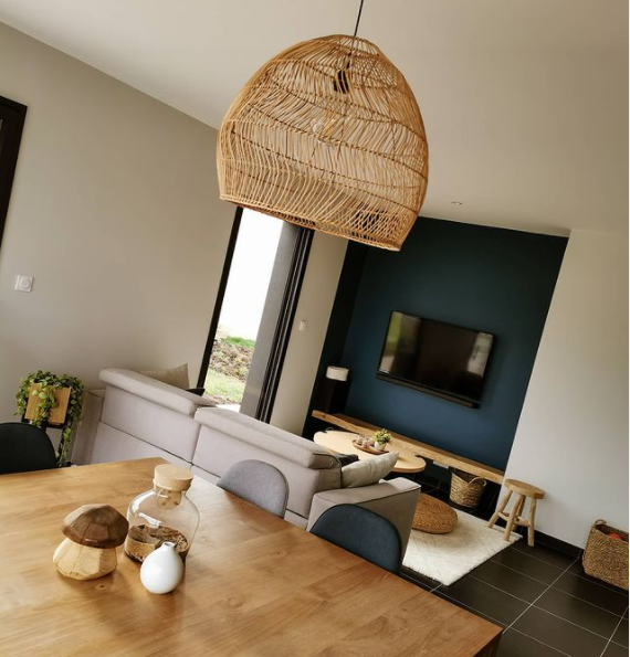A pretty rattan lamp hangs above a wooden dining table