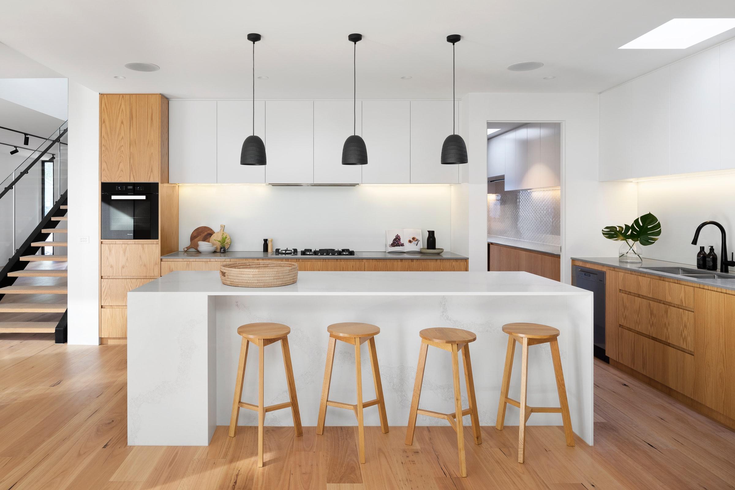 Cuisine simple et épurée de style scandinave. Les armoires et tabourets sont en bois, le comptoir est blanc.