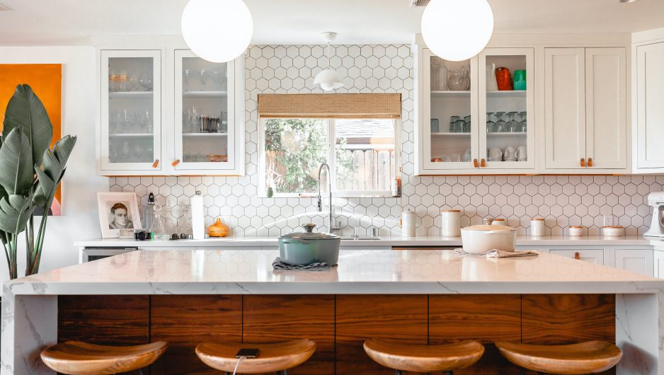 Modern kitchen lit by two pendant lights in the shape of domes.