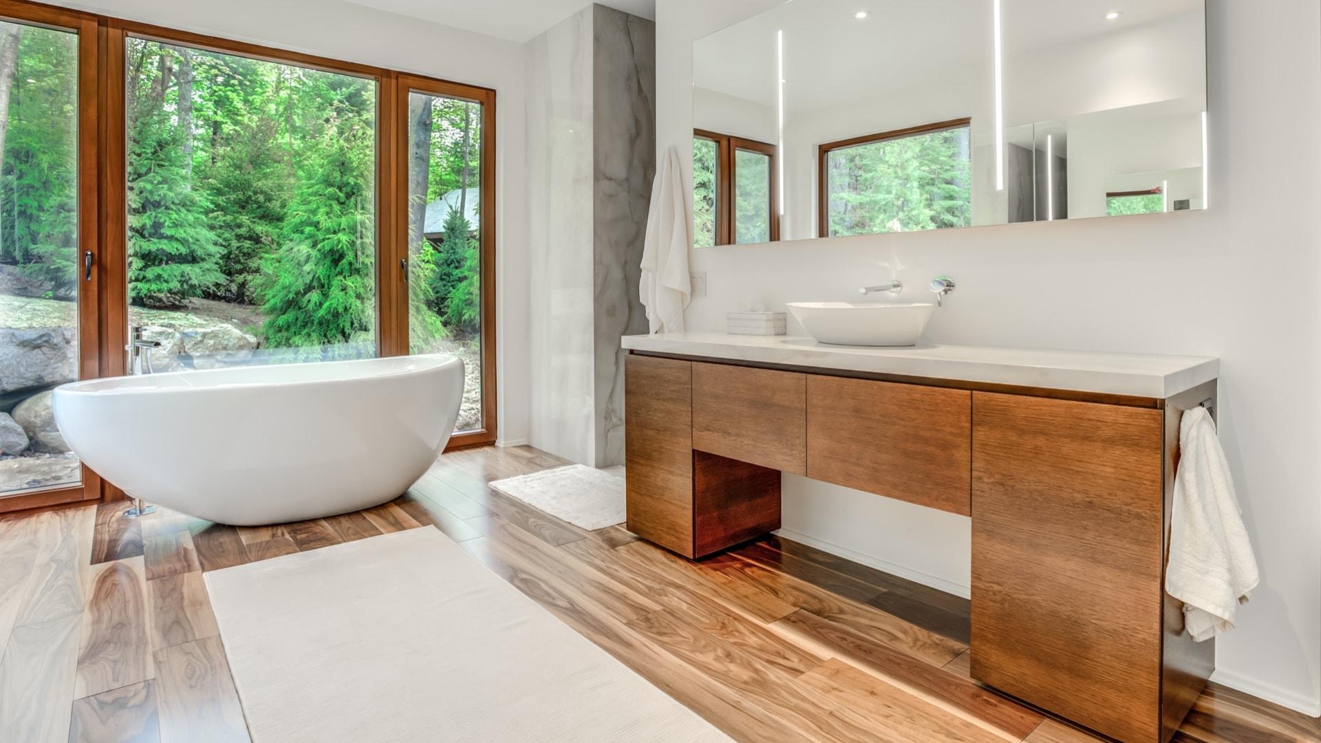Salle de bain contemporaine en placage de chêne. Une grande baignoire autoportante tient place devant de grandes baies vitrées.