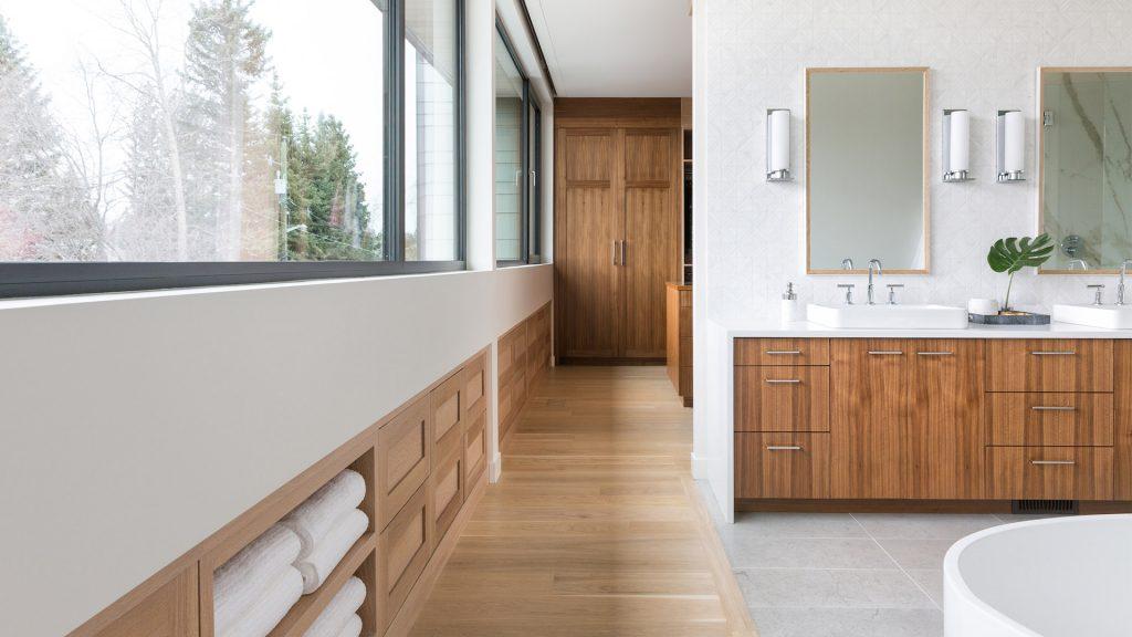 Grande salle de bain avec baignoire. Les comptoirs sont blancs alors que les armoires et le parquet son en bois.