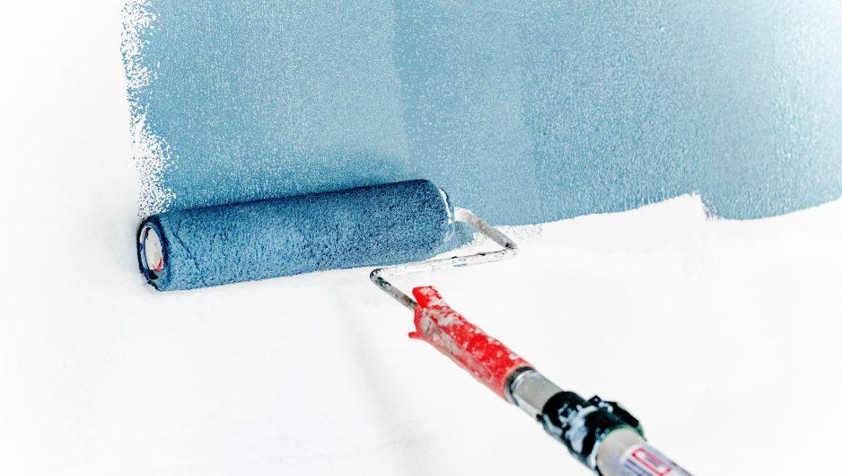 Rouleau de peinture bleue en action sur un mur blanc