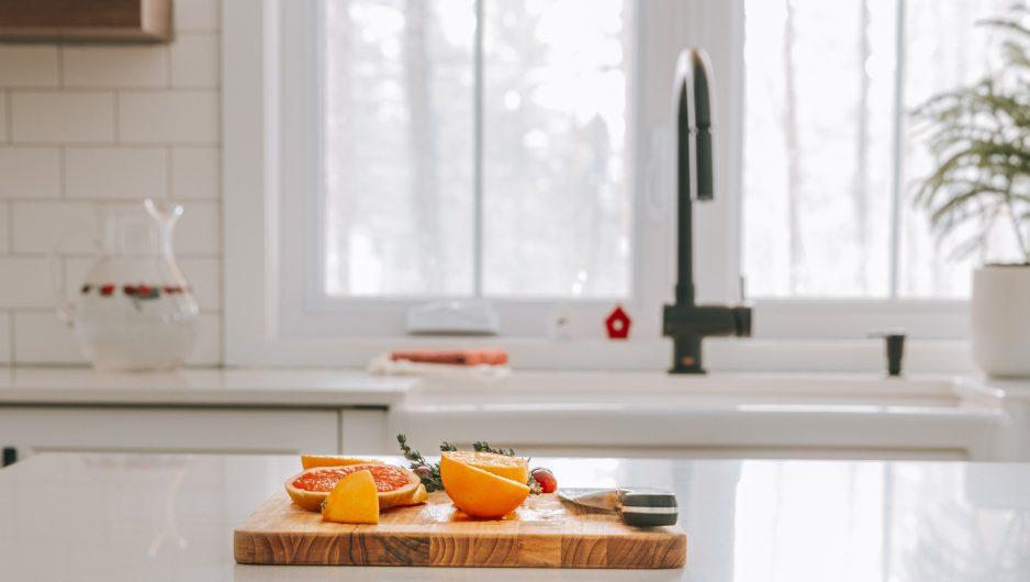 Plan cadré d'une cuisine Ateliers Jacob. Une planche à découper avec des mandarines est disposée sur le comptoir de l'îlot central. La cuisine est trés épurée et blanche.