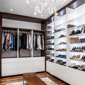 Le walk-in se compose de panneaux de polymère d'un blanc lustré qui reflètent bien la lumière des LED incrustées dans les armoires. Les rangements sur le mur de droite sont des présentoirs à chaussures alors que celui du fond est une penderie de vêtements. Un banc en bois est installé au milieu de la pièce.