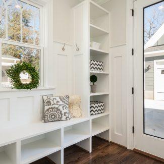 Mudroom dans le hall d'une maison comportant des armoires, des portants et un banc.