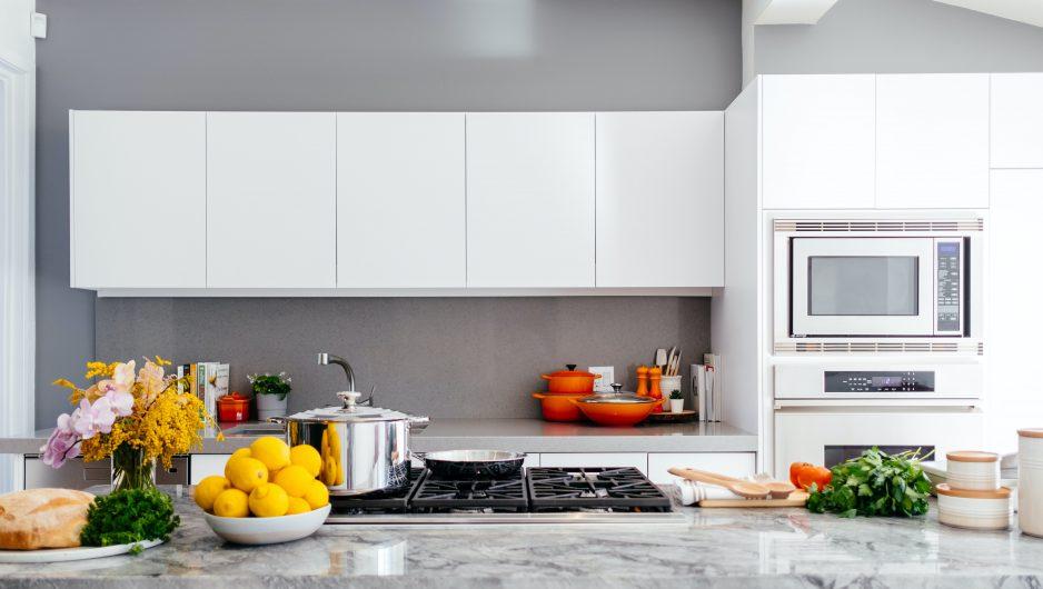 Comptoir de cuisine sur lequel sont disposés différents ustensiles et quelques fruits et légumes.